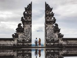 Couple in Pura Lempuyang temple Gate with mirror reflection. Touristic symbol of Bali. Wearing traditional balinese sarong.