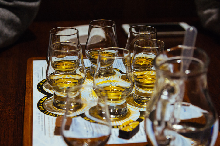 A whisky tasting flight of six glasses on a table