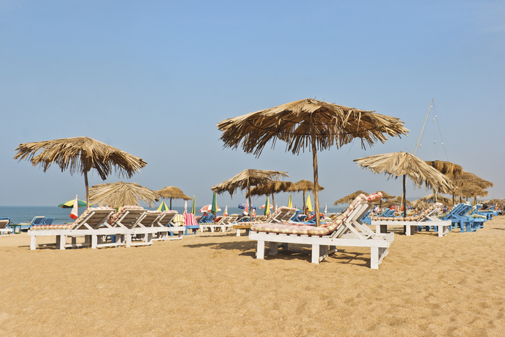 Landscape of Calangute beach resort in Goa India with a  beach scene loungers, sand, sun, parasols,  sea and blue cloudless skies