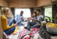 Group of friends having fun playing cards in caravan, games to play in the car