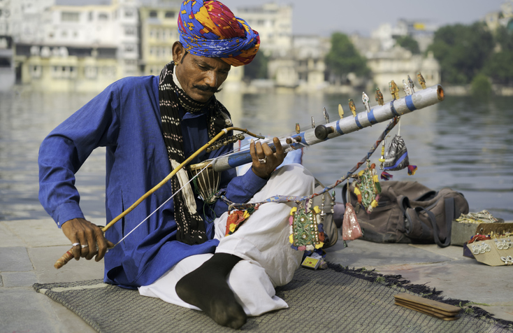 Rajasthani musician playing traditional instrument by the lake in Udaipur