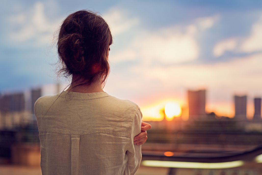 Girl looking at the sunset because she is lost
