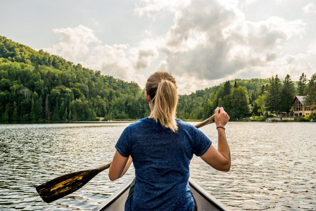 A woman paddling on a lake, ecotherapy