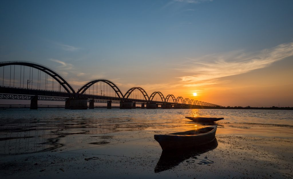 Sunset at Rajahmundry Pushkar ghat, andhra pradesh , in godawari river, with godawari old rail bridge view with orange and blue colour sky and with boats in foreground