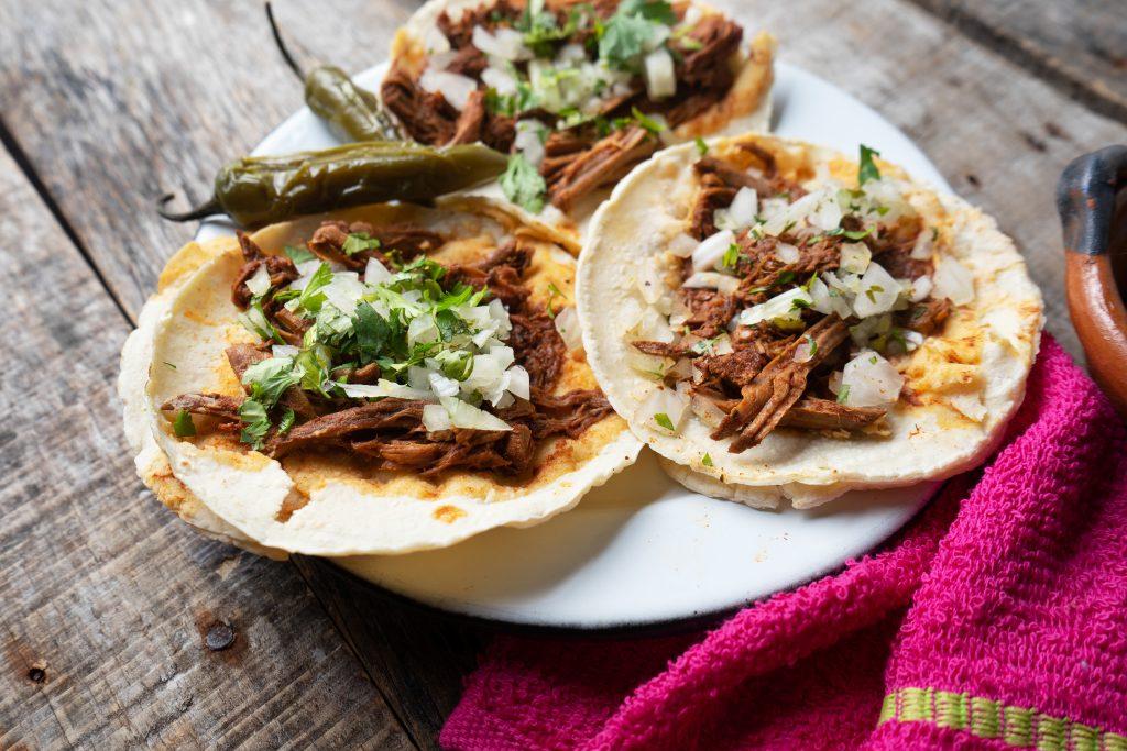 Mexican birria tacos with onion and cilantro