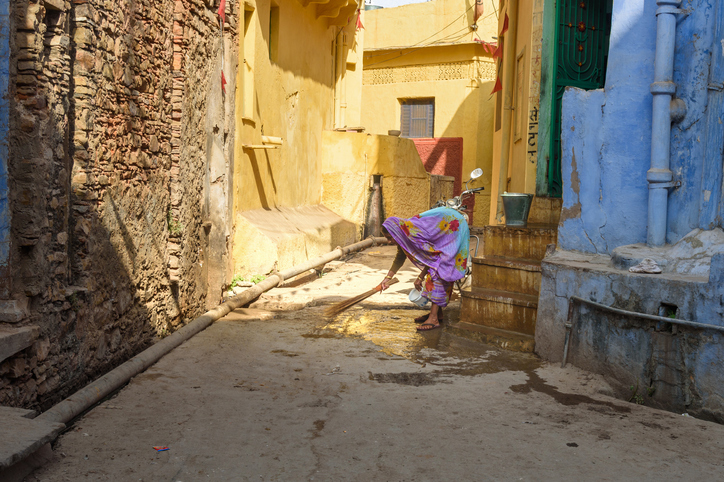 Woman sweeping the street outside her home in India
