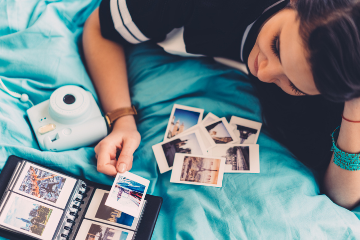 Woman in bed arranging photos from past travels