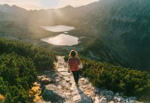 Young Caucasian woman walking near Morksie Oko lake in mountains in Poland