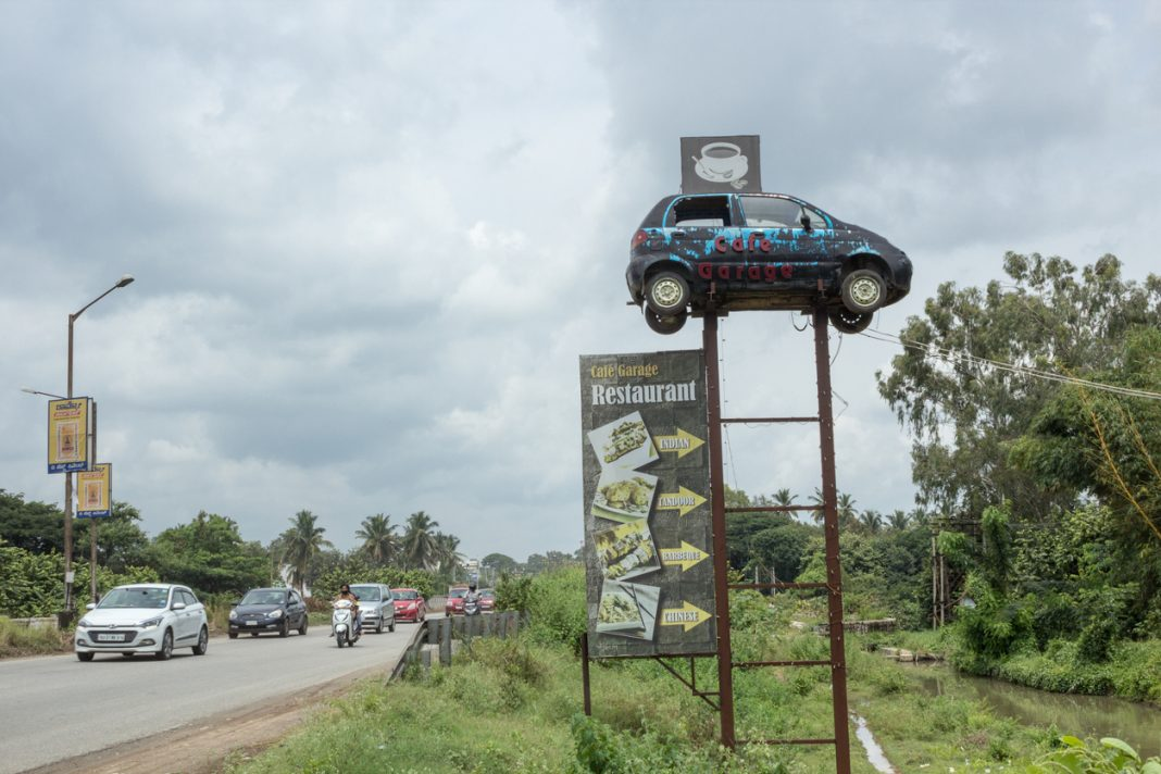 Restaurants in Mysore, An Innovative Advertising strategy by placing a Car on a High point in front of a Highway Cafe near Mysore in Karnataka state of India.