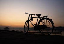 A bicycle in the banks of a river at sunset