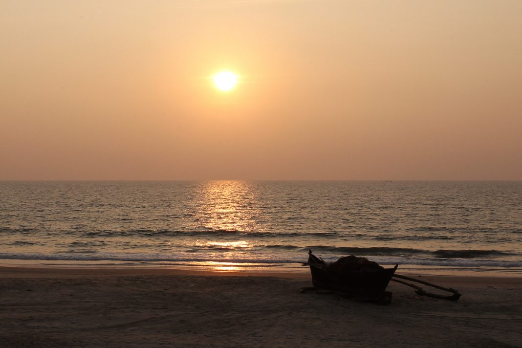 beaches in south goa, A silhouette of a fishing boat on the beach as the sun sets at Colva Beach in Goa, India