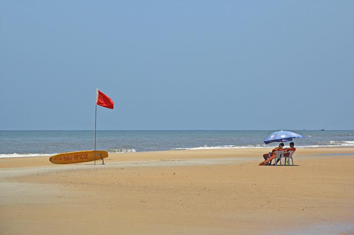 Mobor Beach, Goa, India - September 01, 2017: Two life guards keep vigil under a sun umbrella at Mobor Beach in Goa, India.