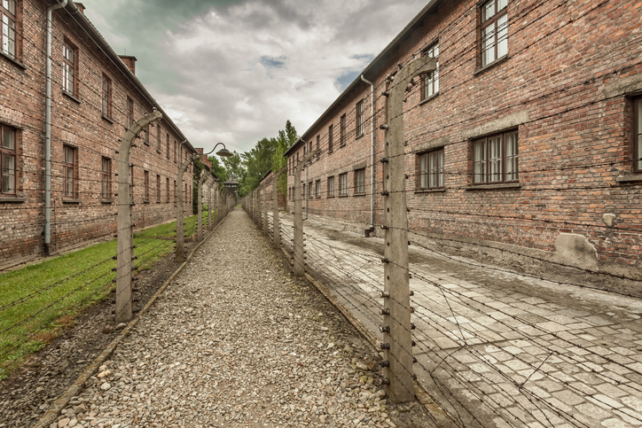 Oswiecim, Poland - June 28, 2015: Barbed wire fence and brick buildings (so called blocks) in Auschwitz I