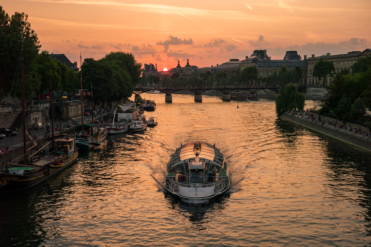Sunset on the historic center of Paris with the river Seine and a riverboat in the foreground, River Cruises