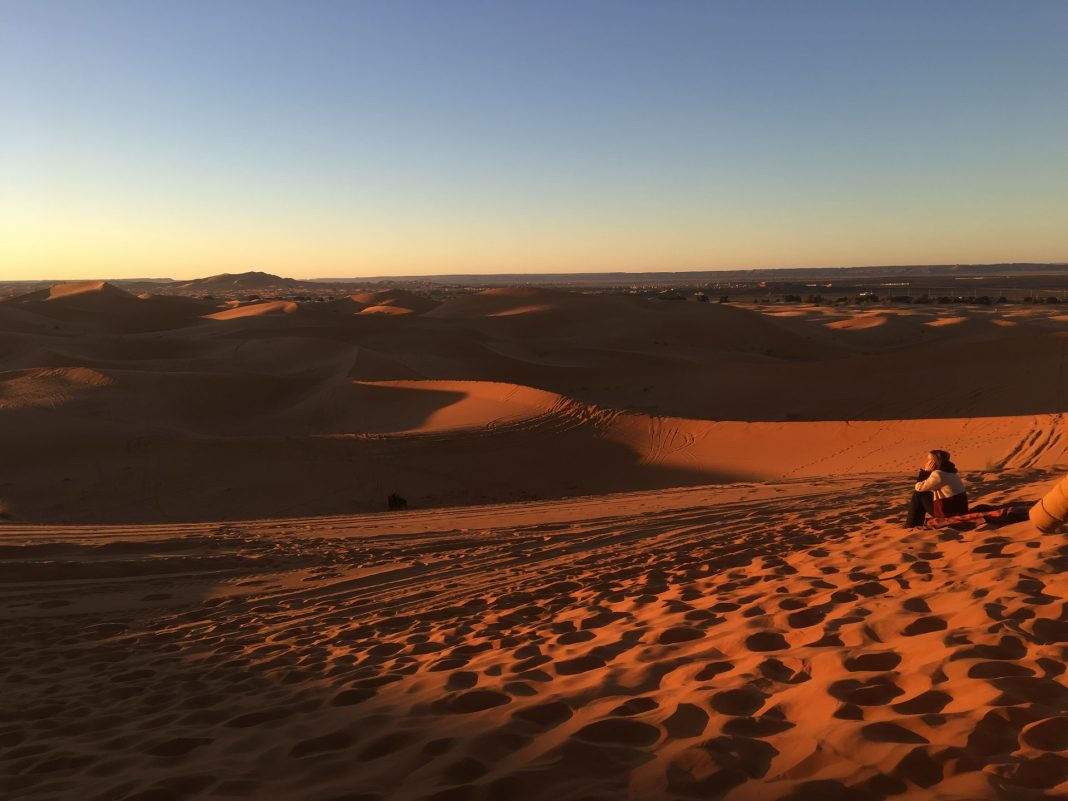 Watching the sunrise while camping in the Sahara