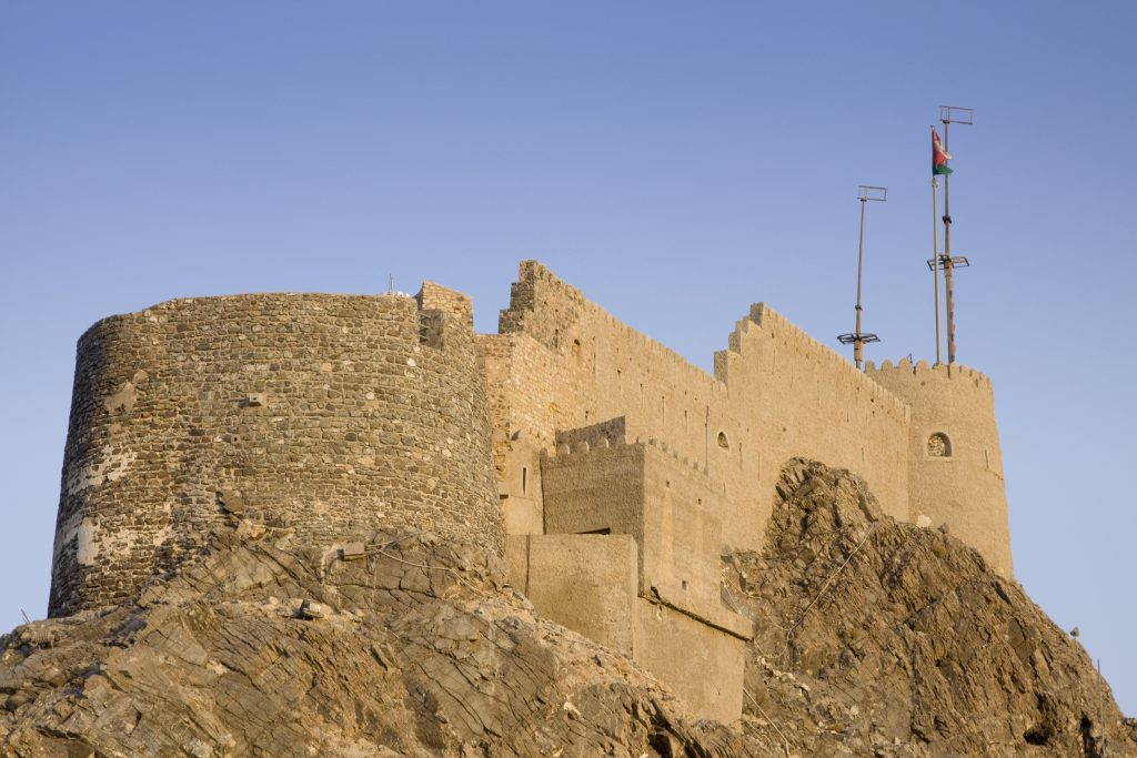 """Mutrah fort on the top of a hill overlooking the harbour of Muscat, Oman just before sunset."""""""