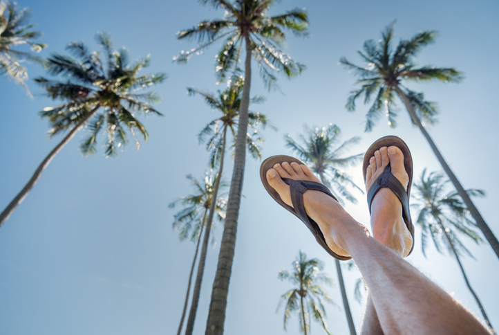 Feet pointing up the clear tropical blue sky with a wonderful palm tree background.