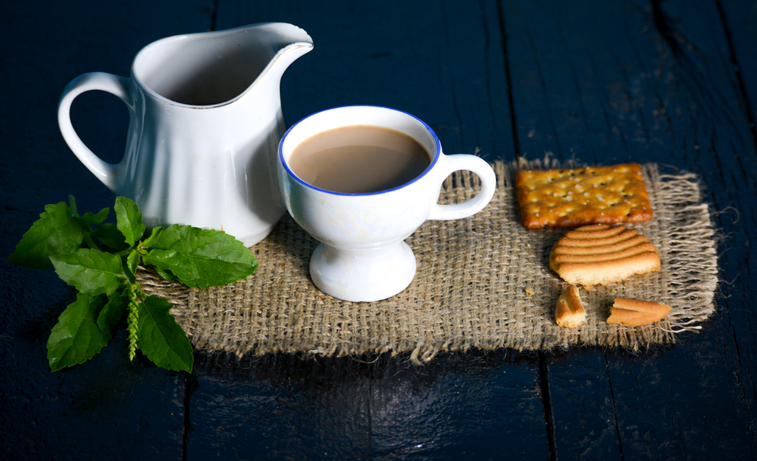 A cup of tea with tasty biscuits, teapot and fresh Leaves on old wooden dark background