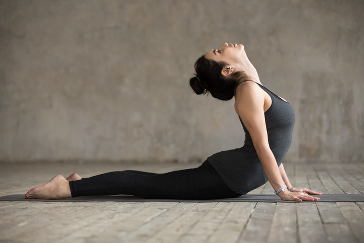 Young woman practicing yoga, doing Cobra exercise, Bhujangasana pose, working out, wearing sportswear, black pants and top, indoor full length, gray wall in yoga studio