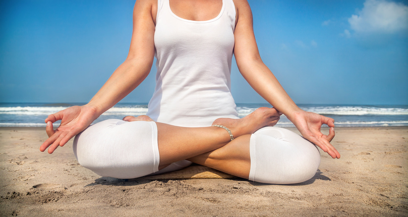 Woman doing yoga meditation in white costume on the beach in Goa, India, Lotus position