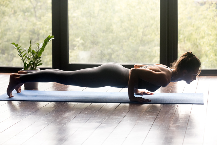 Young woman practicing yoga, doing four limbed staff, Push ups or press ups exercise, chaturanga dandasana pose, working out, wearing sportswear, grey pants and top, indoor full length, yoga studio