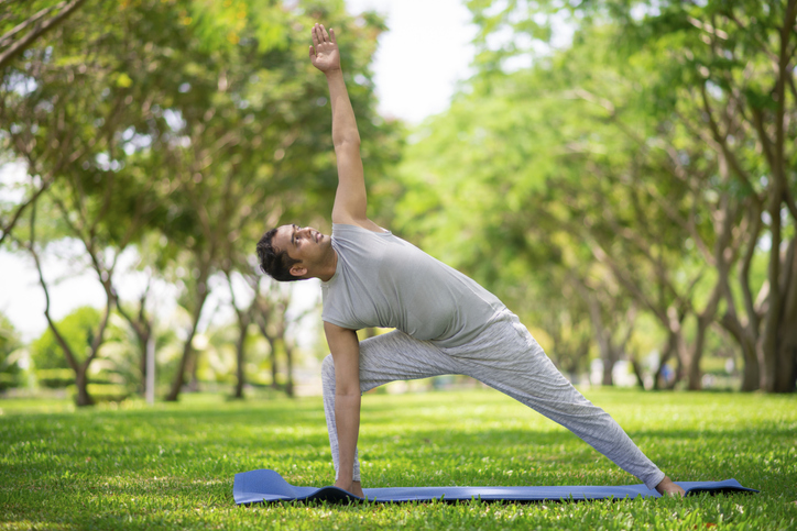 Young citizen exercising outside and standing in yoga side angle pose.