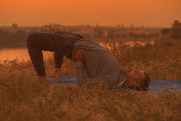 Man doing yoga on sunset with city view, Setu Bandha Sarvangasana/Supported Bridge Pose.
